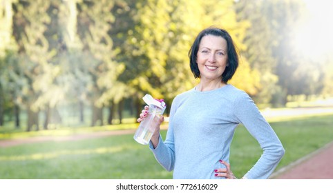 Sporty mature woman hold bottle with water outdoor on sunny day in the park. Healthy lifestyle concept