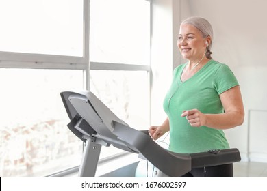 Sporty mature woman on treadmill in gym