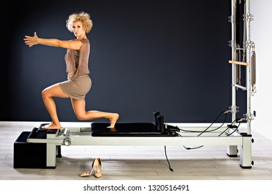 Sporty middle aged woman doing yoga practice on tower reformer - concept of healthy life and natural balance between body and mental development.