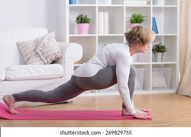 Sporty middle aged woman stretching her body