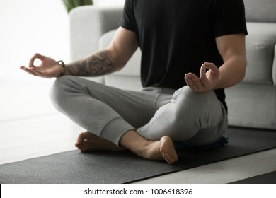 Sporty mindful man with tattoo meditating alone at home, peaceful calm hipster fit guy practicing yoga in lotus pose indoors holding hands in mudra, freedom and calmness concept, close up view