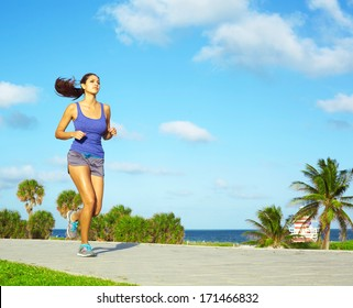 Sporty mixed race woman jogging. Color image, copy space, asian ethnicity female running with green grass and blue sky.