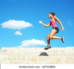 Sporty mixed race woman jumping. Color image, copy space, african american ethnicity female jumping up stairs