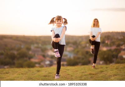 sporty mother and daughter. woman and child training in the park. outdoor sports. healthy sport lifestyle. fitness, yoga.
