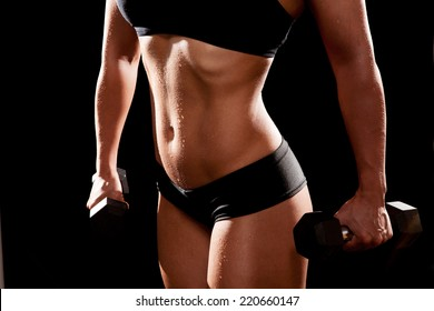 Sporty muscular woman with two dumbbells. On black background.