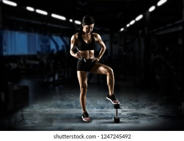 Sporty muscular woman working out with barbell