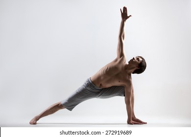 Sporty muscular young man working out, yoga, pilates, fitness training doing lunge exercise, Revolved Side Angle Pose, Parivrtta Parsvakonasana, gray background, low key shot