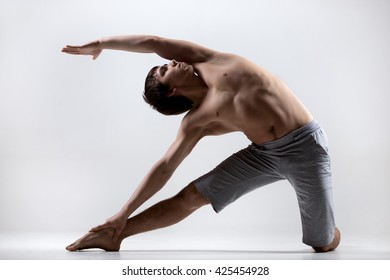 Sporty muscular young man working out, yoga, pilates, fitness training, doing side bend, asana Parighasana, Gate Yoga Pose, gray background, low key shot