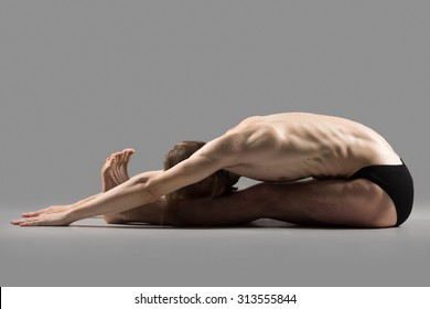 Sporty muscular young yogi man sitting in deep paschimothanasana pose, seated forward bend posture, studio shot on dark background, profile view, full length