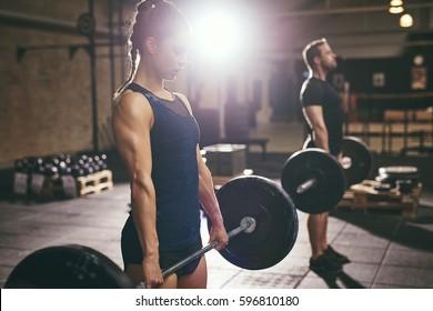 Sporty people deadlifting barbells in gym. Horizontal indoors shot