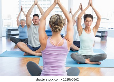 Sporty people with joined hands over heads at fitness studio