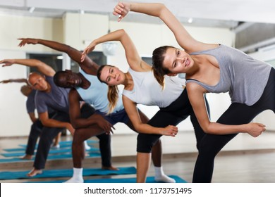 Sporty people practicing stretching before dance training in modern class