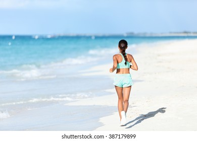 Sporty runner in running outfit training cardio jogging on sunny beach. Unrecognizable person exercising legs and body on white sand next to ocean waves.