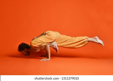 Sporty senior man doing Arm balance exercise for strength, yoga, pilates training, asana Parivritta Eka Pada Koundinyasana, twisted one legged arm balance posture, Crow variation