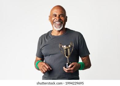 Sporty senior man holding a golden trophy - Shutterstock ID 1994229695