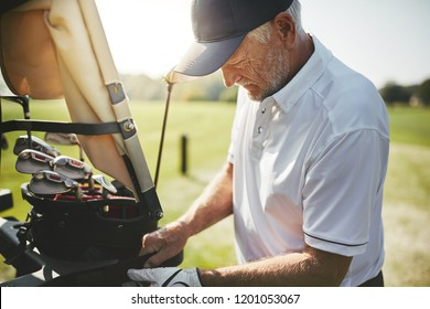 Sporty senior man placing his bag full of clubs on a cart while enjoying a round of golf on a sunny day