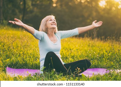 Sporty senior woman enjoys with her arms outstretched  in the nature.Image is intentionally toned.