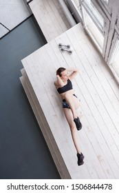 Sporty serious woman doing exercise in gym on floor, sporty girl twisting, touching elbow to knee, raising legs, fitness trainer preparing new fitness program, top view