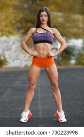Sporty sexy girl with flat belly workout, outdoors. Slim athletic woman in the stadium, abs