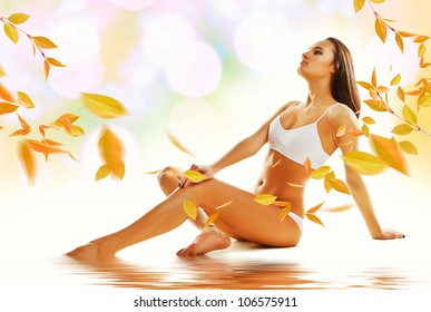 Sporty sexy woman siting on the floor with yellow leaves