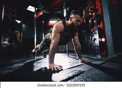 Sporty shape bodybuilder guy in military vest doing push-ups exercise in the gym.