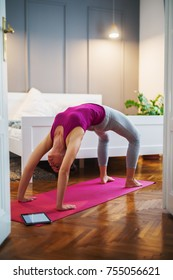 Sporty shape middle aged woman in sportswear doing yoga Bridge exercise on a pink mat in Urdhva Dhanurasana pose in the bedroom at home or hotel with a tablet near.
