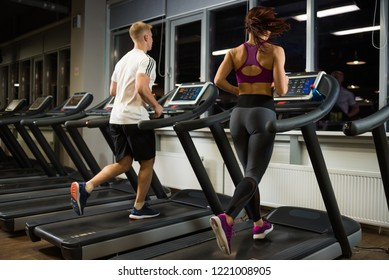 Sporty and slender couple running on the treadmills
