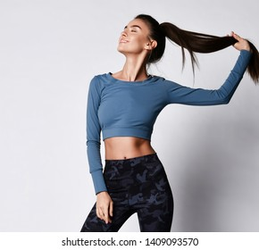 Sporty slim brunette with ponytail fitness woman enjoys workout exercise in purple sport wear on gray background