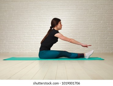 Sporty slim woman doing fitness exercises in the studio on a brick wall background