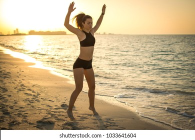 Sporty slim young woman workout at the beach.