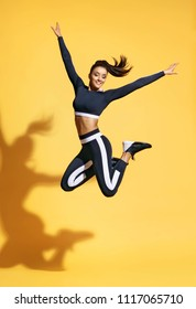 Sporty smiling woman jumping up in silhouette on yellow background. Dynamic movement. Sport and healthy lifestyle