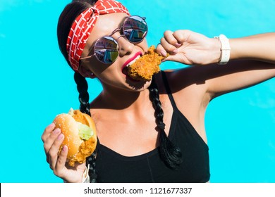 sporty stylish girl in tights, a black top, a bandage on hair, stands on the background of a colored wall. He eats a burger and a piece of fried chicken, drinks soda. Strong emotions, smile, fast food