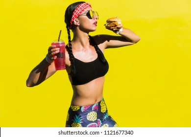 Sporty stylish girl in tights, a black top, a bandage on her hair, stands on the background of a colored wall. He eats a burger and drinks a soda. Strong emotions, smile