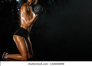 Sporty tanned woman with perfect shape lifting dumbbells on dark background with copy space.