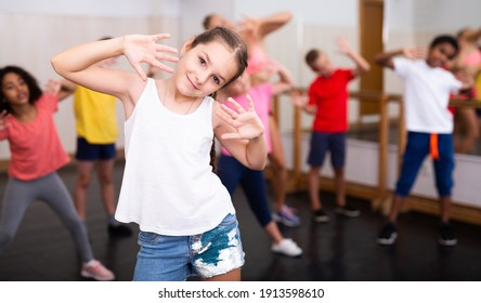 Sporty ten years old girl training movements of vigorous dance during group class in dance school..
