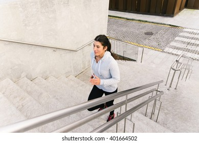 Sporty urban woman running and climbing stairs. Female athlete on hiit workout.