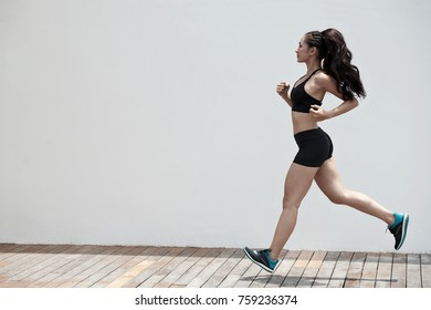 Sporty Vietnamese fit girl running in the morning