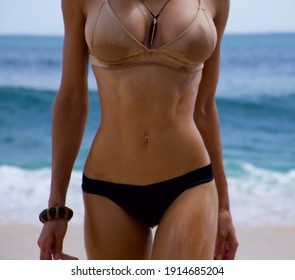 Sporty wet female body on the beach in a swimsuit in a bikini on the background of the ocean.  press