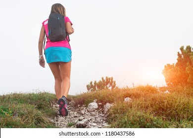 Sporty woman with backpack on walk in the mountains.