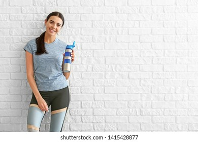 Sporty woman with bottle of water near brick wall