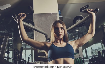 sporty woman builds muscle arms and chest on the simulator in the gym.