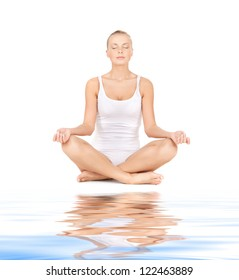 sporty woman in cotton undrewear practicing yoga lotus pose on white sand