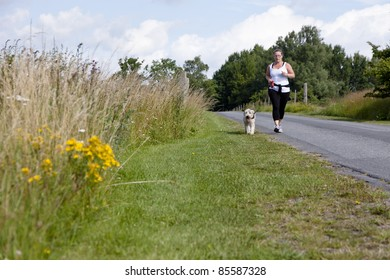 Sporty woman and dog jogging along a road in summertime