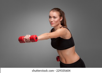 Sporty woman doing aerobic exercise with red dumbbells on grey background