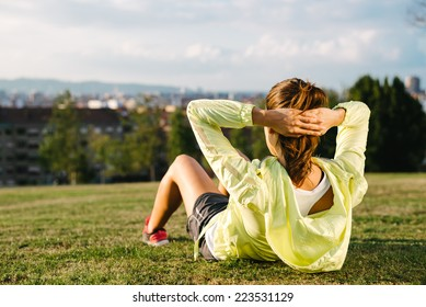 Sporty woman doing crunches workout in city park outdoor. Female beautiful athlete exercising doing situps.