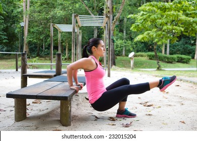 Sporty woman doing dips on left leg in outdoor exercise park