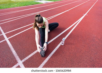 Sporty woman doing exercise at stadium