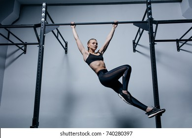 Sporty woman doing exercises on a horizontal bar in the gym