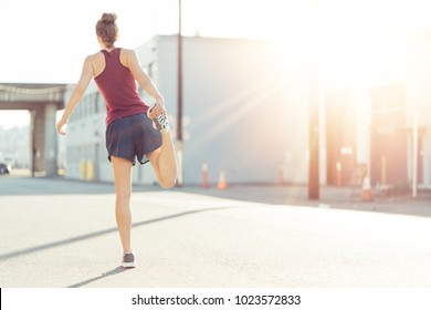 Sporty woman doing morning stretching and warming before city workout session