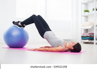 sporty woman doing pilates exercise lifting her pelvis with fit ball at home.